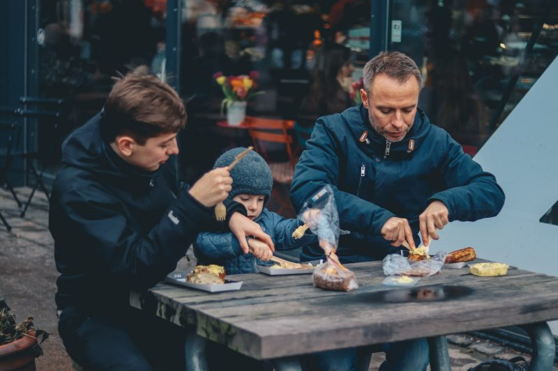 Dos hombres y un niño sentados en una banca satisfaciendo la necesidad básica de comer.
