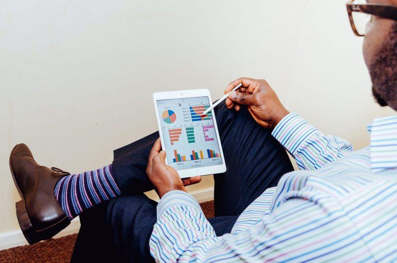 Hombre de negocios viendo un iPad con gráficas