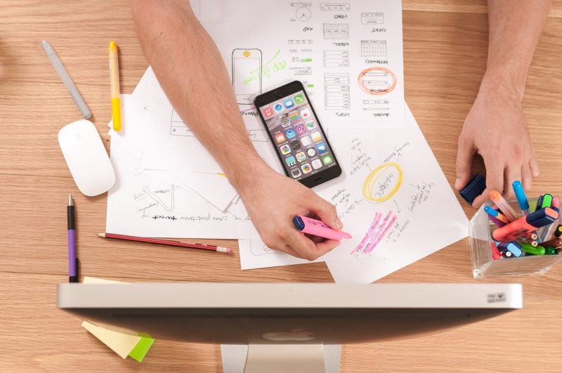 Mesa de trabajo con manos subrayando datos